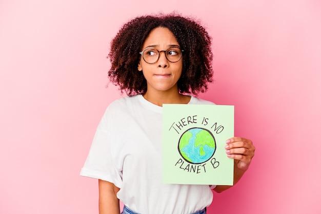 Mulher jovem afro-americana de raça mista segurando um cartão do conceito de proteção mundial confusa, sente-se em dúvida e insegura.