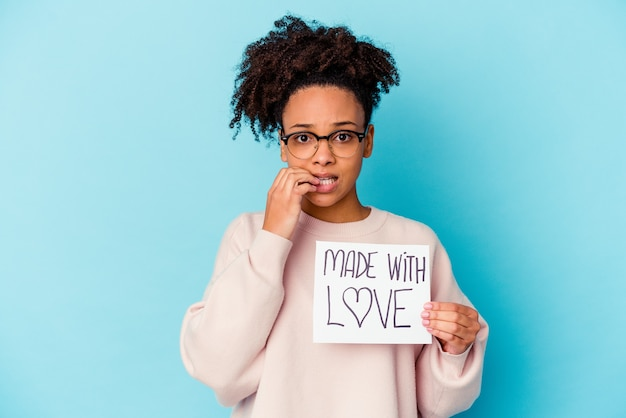 Mulher jovem afro-americana de raça mista segurando um conceito de amor, roendo as unhas, nervosa e muito ansiosa.