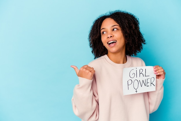 Mulher jovem afro-americana de raça mista segurando um conceito de poder feminino aponta com o dedo polegar para longe, rindo e despreocupada.