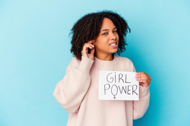 Mulher jovem afro-americana de raça mista, segurando um conceito de poder feminino, cobrindo as orelhas com as mãos.