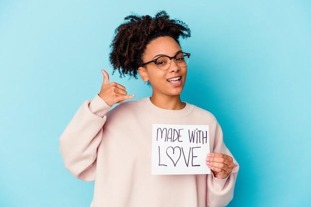 Mulher jovem afro-americana de raça mista segurando um conceito feito com amor, mostrando um gesto de chamada de telefone móvel com os dedos.