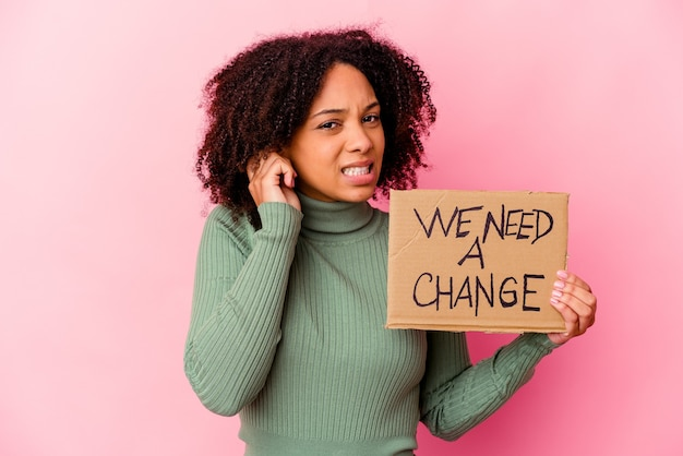 Mulher jovem afro-americana de raça mista segurando um papelão de mensagem inspiradora cobrindo as orelhas com as mãos.