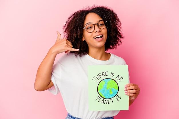 Mulher jovem afro-americana de raça mista segurando um papelão do conceito de proteção mundial, mostrando um gesto de chamada de telefone móvel com os dedos.