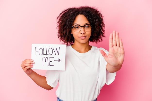 Mulher jovem afro-americana de raça mista, segurando um siga-me conceito em pé com a mão estendida, mostrando o sinal de stop, impedindo-o.