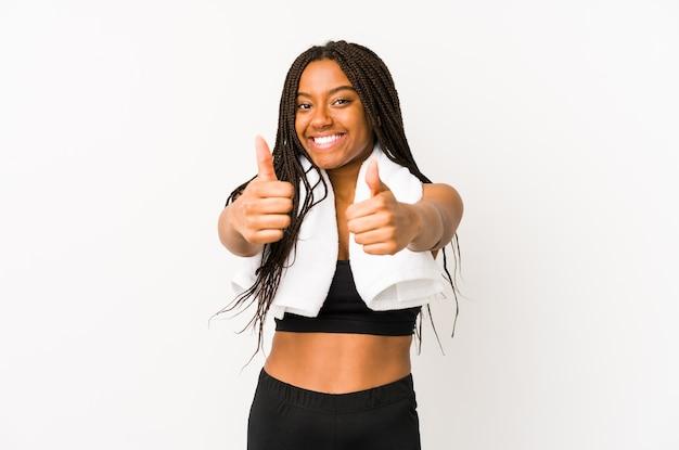Mulher jovem afro-americana do esporte isolada com polegares para cima, aplausos sobre algo