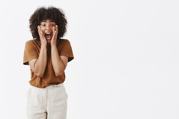 Mulher jovem afro-americana espantada e animada gritando e segurando as mãos no rosto, emocionada e entusiasmada
