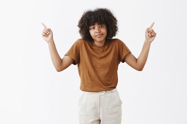 Mulher jovem afro-americana, incerta e descuidada, com um penteado afro, encolhendo os ombros e levantando os dedos indicadores, apontando para os cantos superiores direito e esquerdo