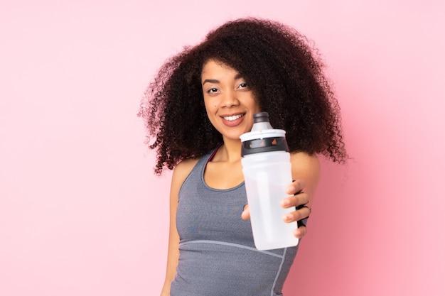 Mulher jovem afro-americana isolada em rosa com garrafa de água esportiva