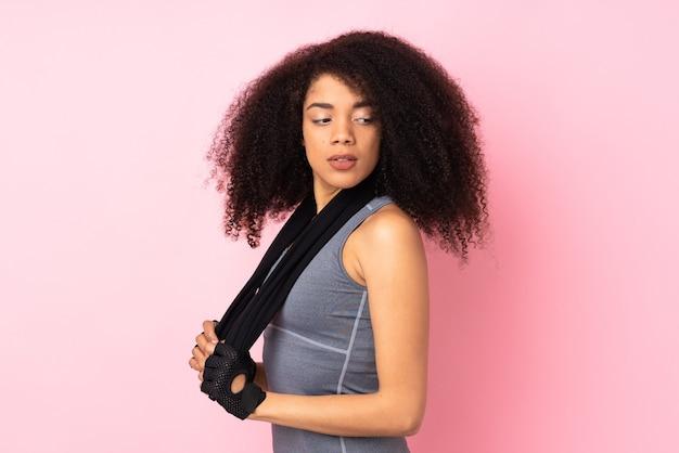 Mulher jovem afro-americana isolada na rosa com uma toalha esportiva