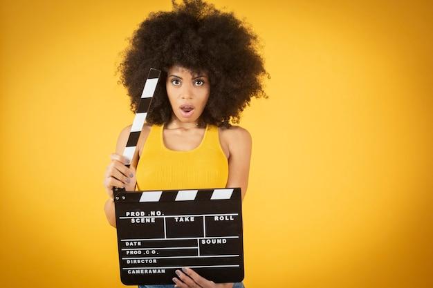 Mulher jovem afro-americana mista, animada, roupa casual, mantendo a boca aberta, segura claquete de filme preto clássico isolada em fundo laranja.