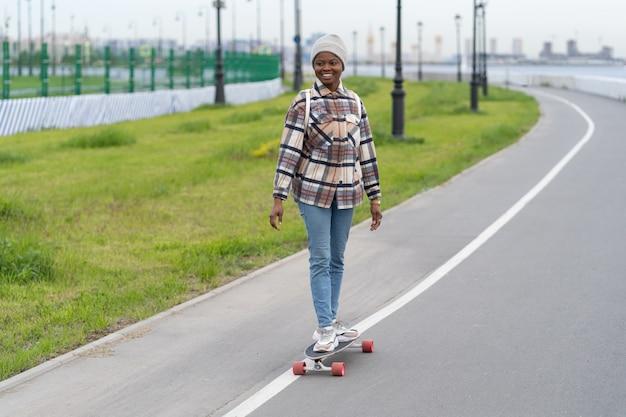 Mulher jovem afro feliz patinando em um longboard sorrindo e relaxando com um skate ao ar livre no espaço da cidade