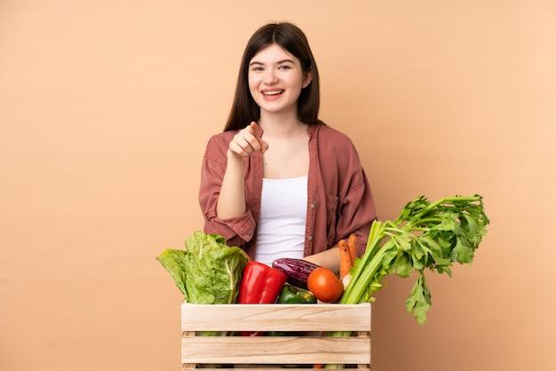 Mulher jovem agricultor com legumes recém colhidos em uma caixa de surpresa e apontando para a frente