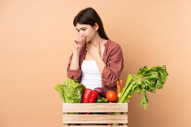 Mulher jovem agricultor com legumes recém colhidos em uma caixa está sofrendo de tosse e se sentindo mal