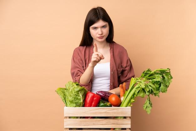 Mulher jovem agricultor com legumes recém colhidos em uma caixa frustrada e apontando para a frente