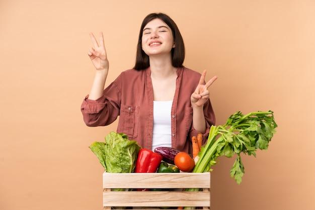 Mulher jovem agricultor com legumes recém colhidos em uma caixa mostrando sinal de vitória com as duas mãos