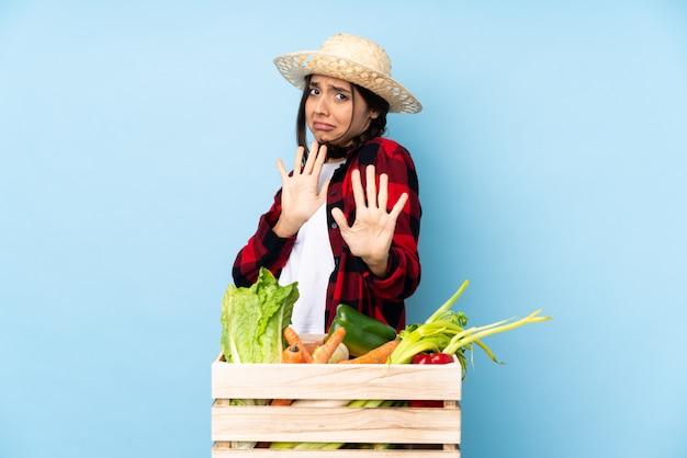 Mulher jovem agricultor segurando legumes frescos em uma cesta de madeira nervosa, esticando as mãos para a frente