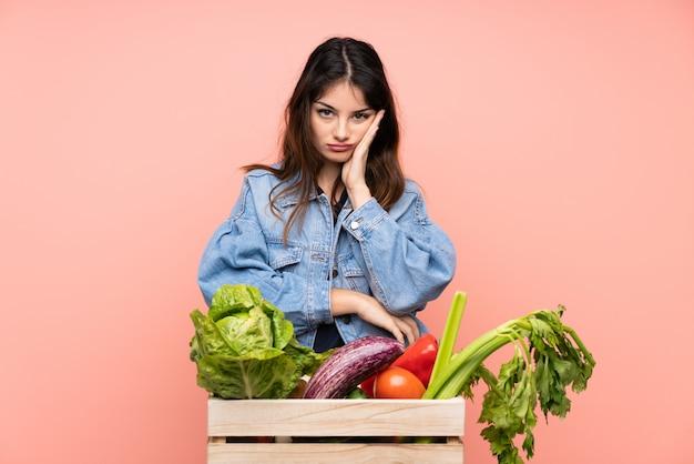Mulher jovem agricultor segurando uma cesta cheia de legumes frescos, infeliz e frustrada
