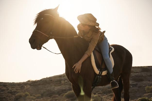 Mulher jovem agricultora cavalgando em um dia ensolarado ao ar livre - foco no rosto
