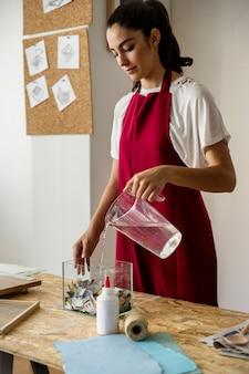 Mulher jovem, água derramando, em, recipiente vidro, enchido, com, rasgado, papeis