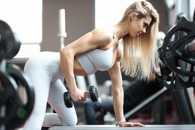Mulher jovem ajoelhada e levantando halteres na academia