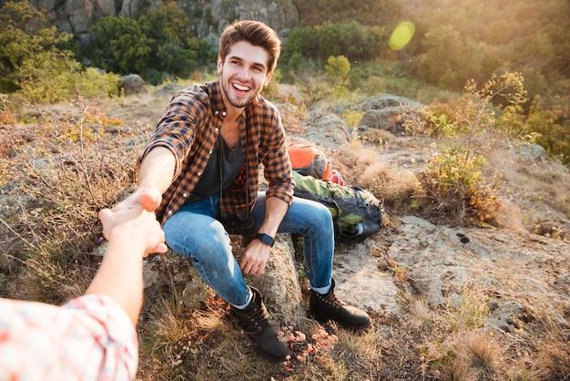 Mulher jovem ajuda o namorado a se levantar em sua jornada de caminhada