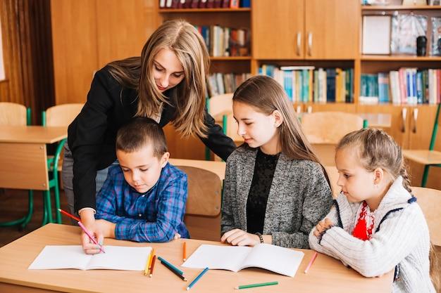 Mulher jovem, ajudando, estudantes, com, tarefa