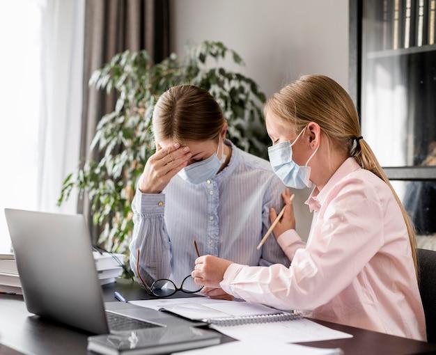 Mulher jovem, ajudando, menina, dever casa, enquanto, desgastar uma máscara médica