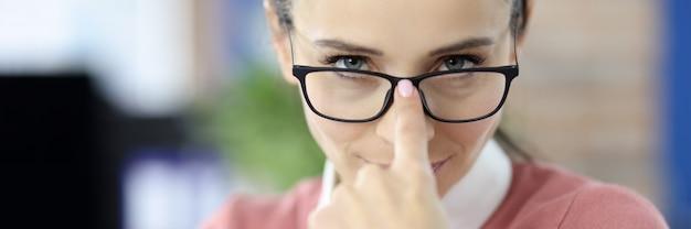 Mulher jovem ajustando os óculos para o conceito de patrões rígidos