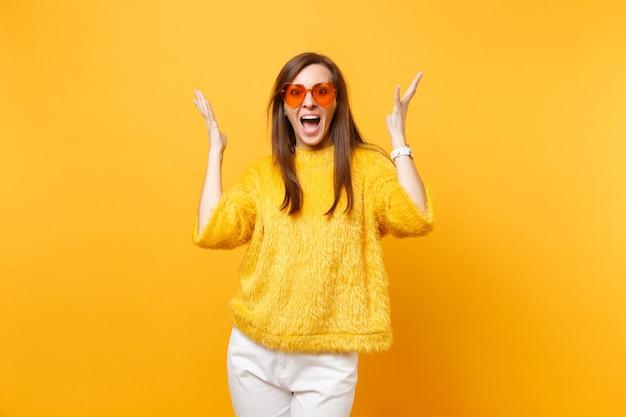 Mulher jovem alegre animada no suéter de pele, calça branca e óculos coração laranja, espalhando as mãos isoladas em fundo amarelo brilhante. emoções sinceras de pessoas, conceito de estilo de vida. área de publicidade.