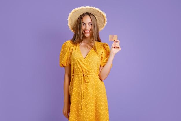Mulher jovem alegre caucasiana em vestido amarelo e chapéu de palha, segurando o cartão do banco isolado no ba roxo.