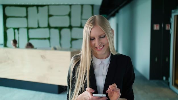 Mulher jovem alegre com telefone no escritório mulher loira bonita com cabelo comprido, vestindo um elegante terno preto e sorrindo encantadoramente para a câmera dentro do escritório moderno