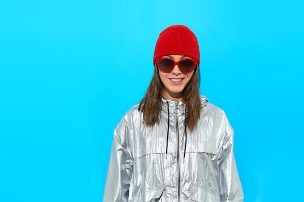 Mulher jovem alegre e ativa em óculos de sol da moda, vestindo uma elegante jaqueta esportiva cinza e chapéu de malha vermelho em pé