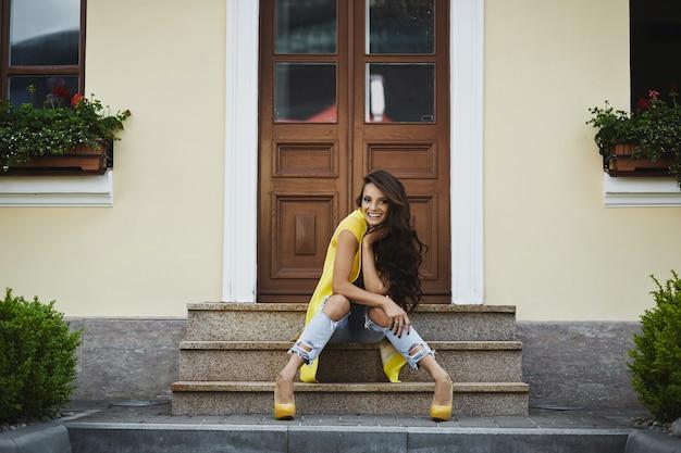 Mulher jovem alegre em roupa casual amarela, sentado na escada, garota modelo feliz ao ar livre, rindo e.