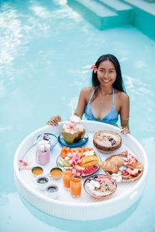Mulher jovem alegre em traje de banho com mesa flutuante cheia de comida tropical nada na piscina em um hotel luxuoso.