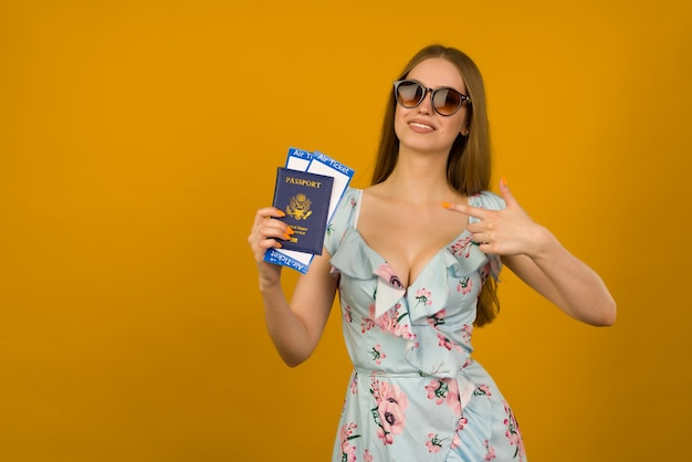 Mulher jovem alegre em um vestido azul com flores e óculos de sol, apontando para as passagens aéreas com um passaporte em um fundo amarelo. alegra-se com a retomada do turismo após a pandemia do coronovírus.