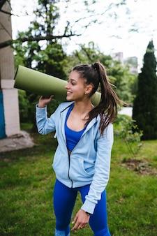 Mulher jovem alegre esportes caminhando no parque urbano, segurando o tapete de fitness.
