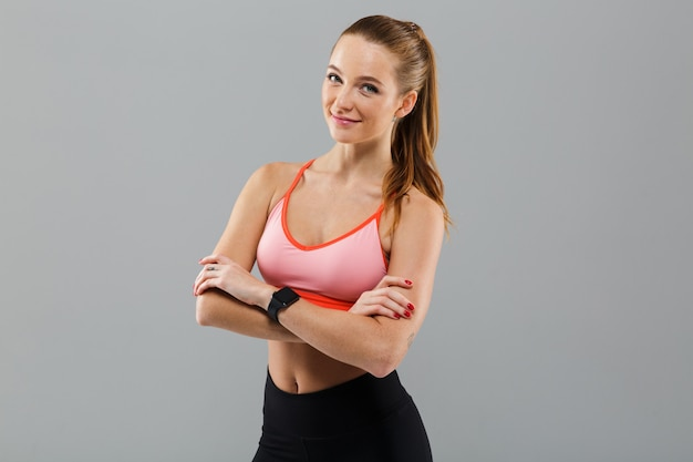 Mulher jovem alegre esportes com braços cruzados.
