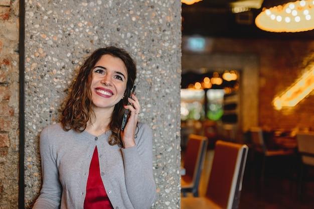 Mulher jovem alegre feliz falando ao telefone, sentado à mesa do restaurante.