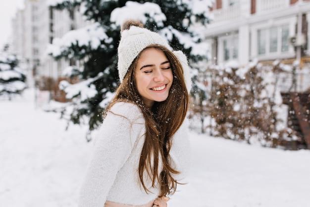 Mulher jovem alegre retrato com longos cabelos castanhos, se divertindo na rua cheia de neve. gorro de malha, suéter de lã branca, sorriso incrível, olhos fechados, curtindo o inverno.