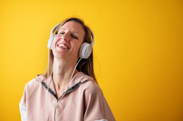 Mulher jovem alegre rindo com alegria enquanto ouve música com os fones de ouvido na cabeça.