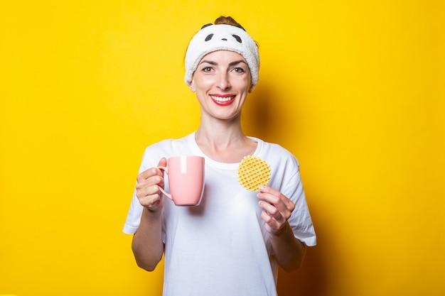 Mulher jovem alegre sorridente com uma xícara de café e waffle belga em fundo amarelo.
