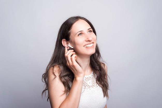 Mulher jovem alegre sorrindo e usando fones de ouvido na parede branca.