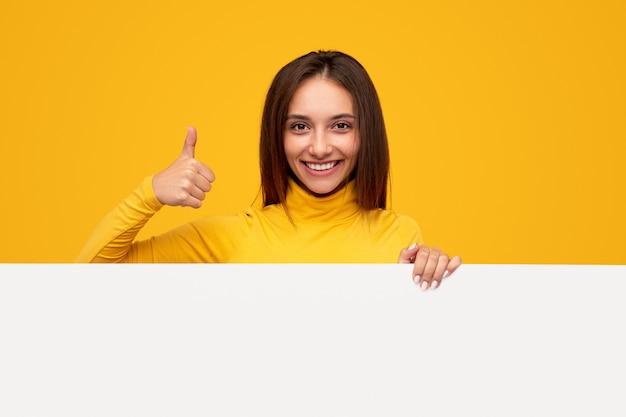 Mulher jovem alegre sorrindo para a câmera e aprovando um banner em branco com gesto de polegar para cima durante campanha publicitária contra fundo amarelo