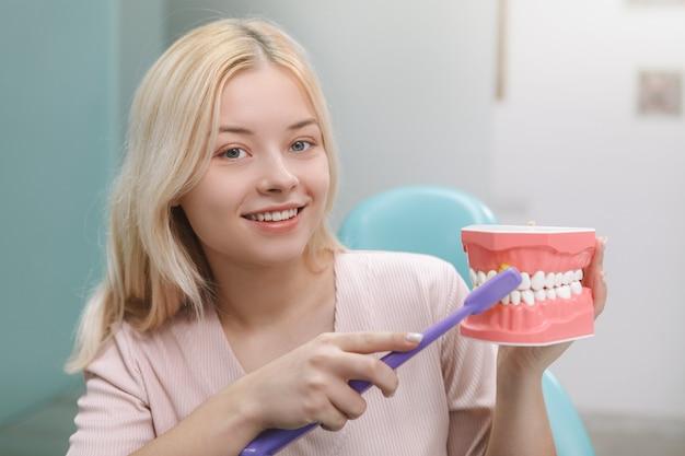 Mulher jovem alegre sorrindo para a câmera enquanto mostra como escovar os dentes corretamente em um modelo de mandíbula
