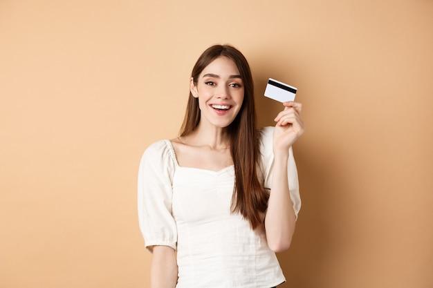 Mulher jovem alegre tem seu cartão de crédito de plástico e sorrindo satisfeito em pé satisfeito no bac bege.