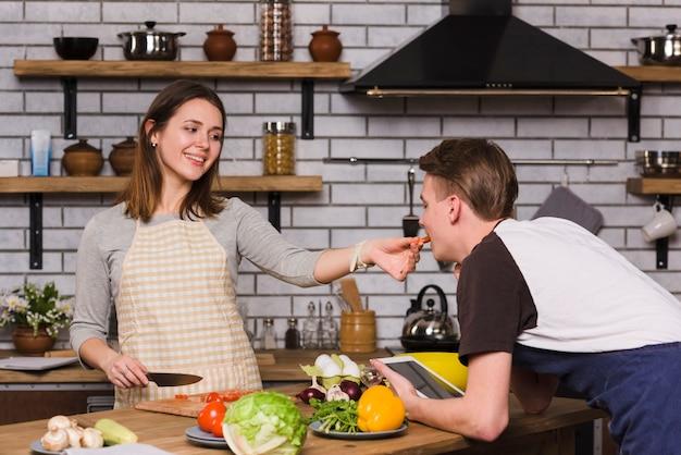 Mulher jovem, alimentação, namorado, com, tomate cortado