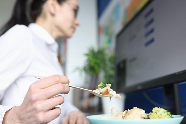 Mulher jovem almoçando não desvie o olhar do monitor do computador