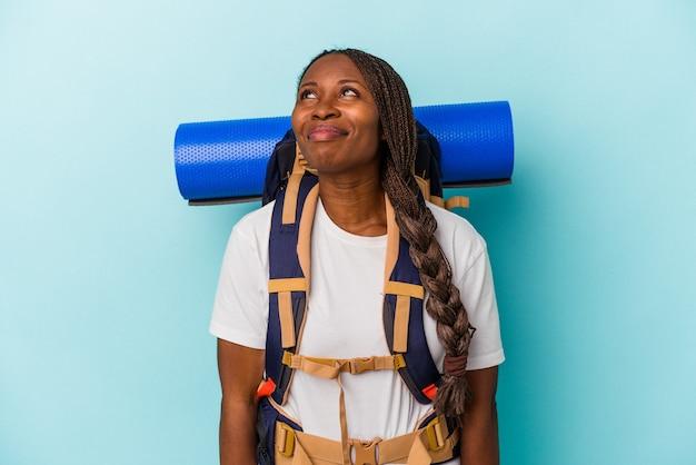Mulher jovem alpinista afro-americana isolada em um fundo azul, sonhando em alcançar objetivos e propósitos.