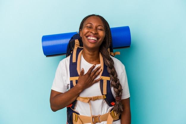 Mulher jovem alpinista afro-americana isolada sobre fundo azul ri alto, mantendo a mão no peito.