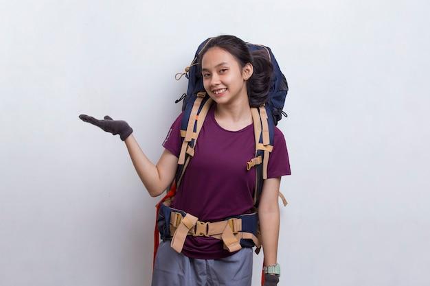 Mulher jovem alpinista asiática com mochila apontando o dedo no espaço vazio no fundo branco